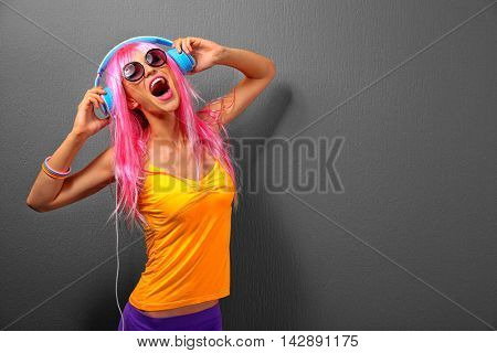 Glamour young woman with headphones on grey background