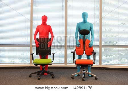 anonymous couple in full body elastic suits standing behind armchairs in office space