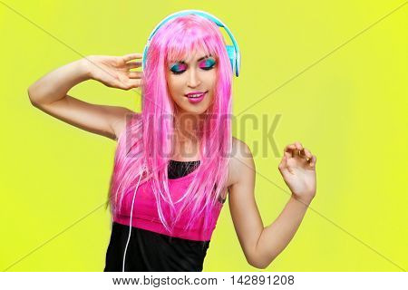 Glamour young woman with headphones on yellow background