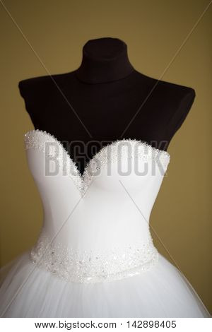 Wedding white dress traditional bridal model with beautiful fashion elegant strapless corset beaded with beads hanging on black mannequin studio