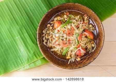 papaya salad (papaya pok pok) top view on a wooden table and green banana leaf Thai local food.
