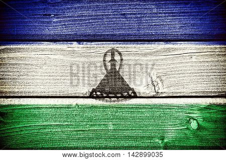 flag of Lesotho painted on old grungy wooden background: 3d illustration