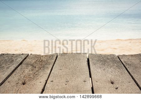 Wooden surface at tropical beach with blurred sea and sandy beach on background