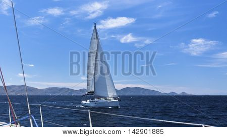 Sailing regatta in the wind through the waves. Luxury yachts.