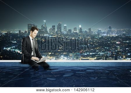 Young businessman using laptop on the edge of rooftop swimming pool with legs in the water. Night city view background