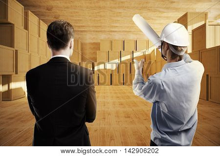 Businessman and constructor discussing warehouse design, close up