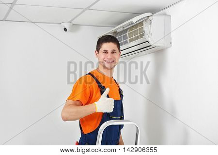 Technician near air conditioner indoor