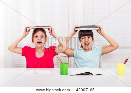 Angry little girls are screaming because they must stay at home and do their homework,but they would rather play outside.