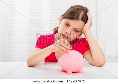 Beautiful little girl is very sad because she didn't save enough money to buy something.