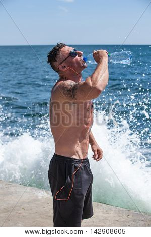 Handsome man drinking water against the sea