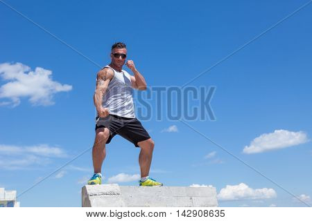 man engaged in karate against the sky