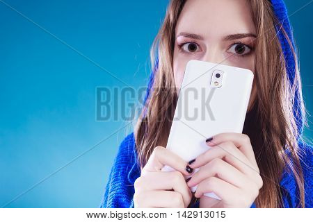 Young woman making big eyes. Hiding behind phone. Pretty girl in sweater.
