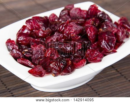 Tasty dried cranberries in small white bowl