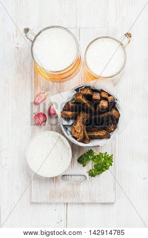 Beer snack set. Two mugs of pilsener, rye bread croutons with garlic cream cheese sauce served with fresh herb and garlic over white painted old wooden background, top view