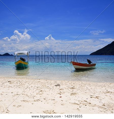 Two boats harboring on the beaches of Perhentian island, Malaysia