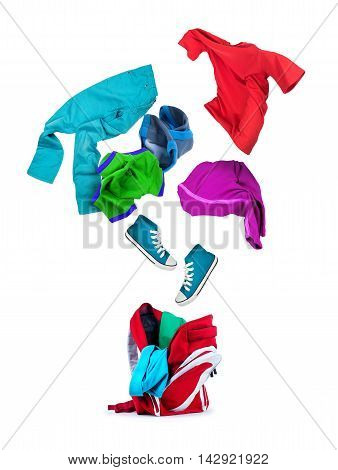 colorful clothing falls into a backpack isolated on white background