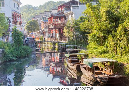 08/12/2016 LikengChina - River leading into the old town of Likeng with old boats and traditional building decorated with red lanterns