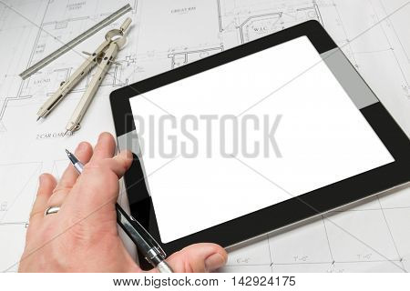 Architect Working on Blank Computer Tablet, Over House Plans, Pencil, Compass. Contains Screen Clipping Path.