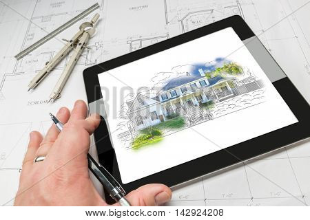 Hand of Architect on Computer Tablet Showing Custom Home Illustration Over House Plans, Compass and Ruler.