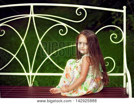 Beautiful little girl with long hair in the summer sitting on a bench and looks straight at the camera mysteriously smiling