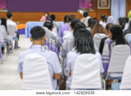 Blurred abstract background of university students sitting in a lecture room with teacher in front of the class