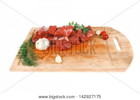 fresh raw beef meat slices over a wooden board with dill , green  and red hot peppers isolated over white backkground