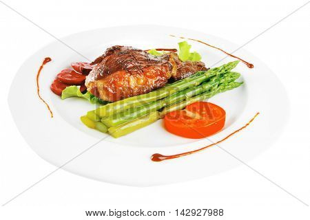 roasted beef meat steack served with asparagus on ceramic plate isolated on white background with asparagus and tomatoe