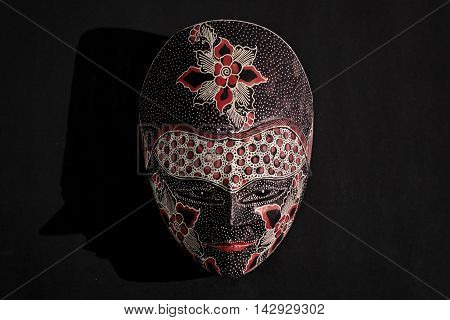 Traditional Javanese batik wooden mask with dark background