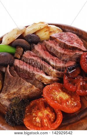 fresh grilled bbq beef meat rib eye steak on wooden plate with baked tomatoes mushroom, potatoes, hot chili pepper isolated on white backgrodun empty space for text
