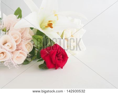 Natural flowers (rose and lily), artificial corsage, on bright white background /Pale image