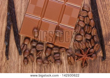 Portion of milk chocolate fresh fragrant vanilla sticks pods star anise and coffee grains on wooden background
