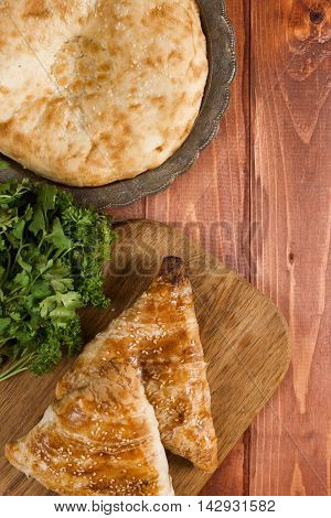 Traditional Uzbek bread and samosas on wooden background