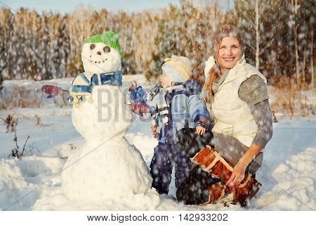 funny mother and baby with a snowman. Family walking under the snow outdoors in winter