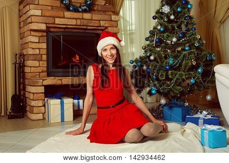 attractive woman in santa hat sitting near the fireplace and decorated Christmas tree. New Year and xmas