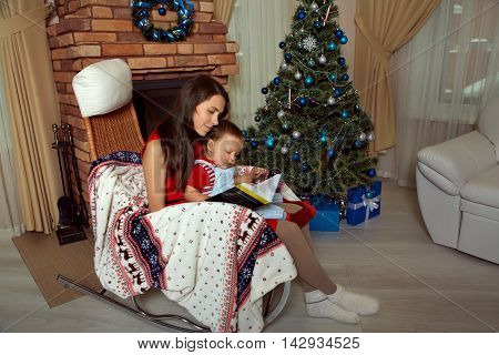 mother and son reading Christmas fairy tales sitting on a chair near the fireplace and Christmas tree. New Year and xmas people