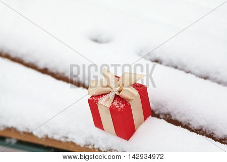 Christmas gift box in the snow outdoors