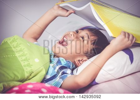 Asian Boy Surprised, Child Covering Head With Book. Vintage Tone Effect.