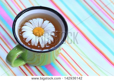 Colorful Cup of Chamomile Tea on a Striped Table Cloth.