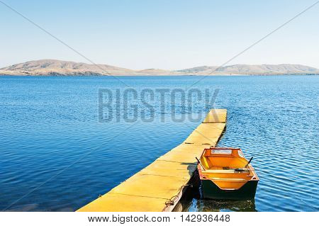 Yellow Pier And Boat On The Lake