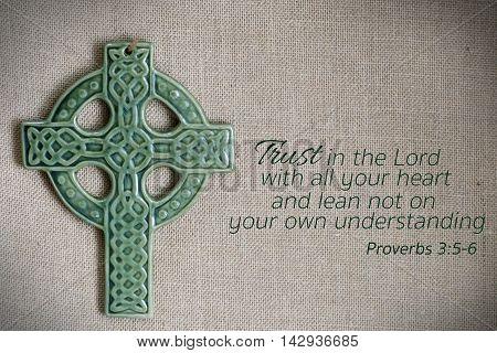 green cross and proverb bible passage on burlap background