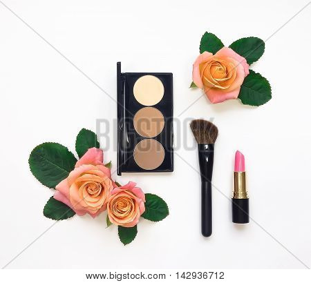 Decorative flat lay composition with woman cosmetics and rose flowers. Flat lay top view on white background make up concept