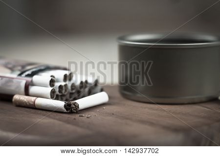 Quit smoking, breaking the cigarette on the wood ( dark tone )