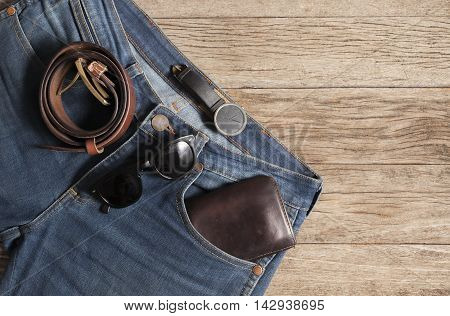 Jeans Wallet and Belt watches glasses on wood backgroundtop view