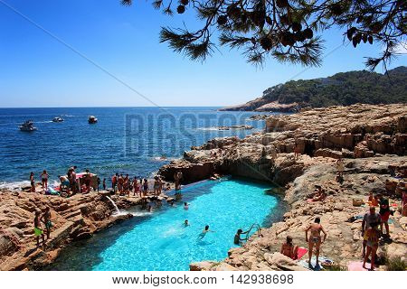 GIRONA/SPAIN - 13 AUGUST 2013: Tourist bathing in a blue natural salty water pool south of the village of Begur in Costa Brava