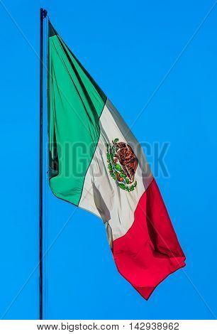 Mexican flag weaving on blue sky .