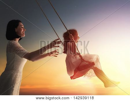 Happy loving family! Young mother and her child daughter swinging on the swings and laughing a summer evening outdoors.