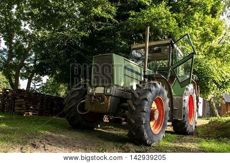 old green tractor under a tree on a farm selected focus narrow depth of field