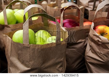 paper bags with organic green and red apples on the market fresh harvest from the farm selected focus on the anterior bag very narrow depth of field