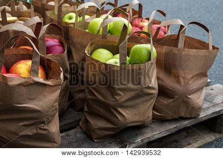 organic green and red apples in brown paper bags for sale on the market fresh harvested from the farm selected focus on the anterior bag narrow depth of field