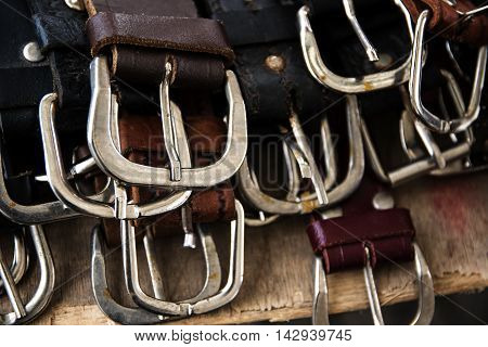 several silver buckles of leather belts for sale at a flea market selected focus narrow depth of field